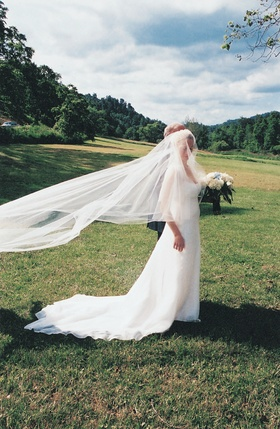 Bride in countryside with bridal veil in wind