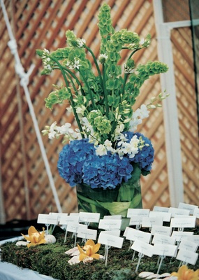 Place cards on green moss surrounded by orchids
