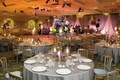 Wedding reception tables covered in silver tablecloths and candelabra centerpieces of purple flowers