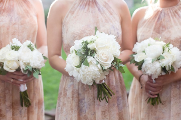 bridessmsaids in high neck printed gowns holding white bouquet peony rose flowers greenery