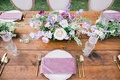 wedding reception rustic wood table purple napkin gold flatware greenery white purple centerpiece