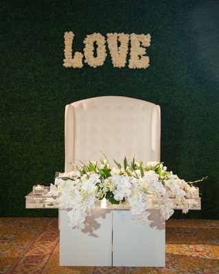 Wedding sweetheart table nfl player levine toilolo wedding love sign in flowers on hedge wall