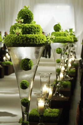 Glass vase with green flower decorations along aisle