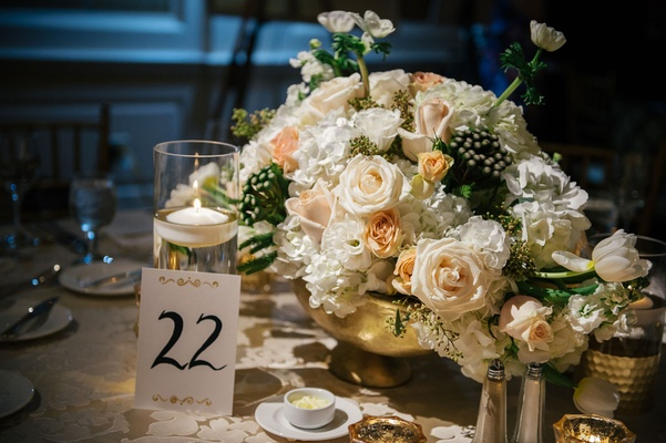 Wedding reception gold vessel vase white peach flowers greenery table number calligraphy gold detail