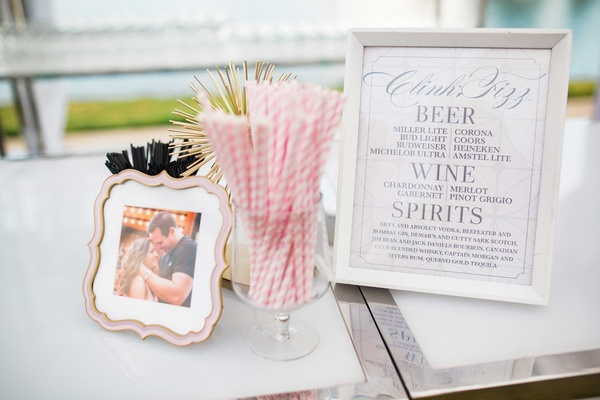 framed bar menu with pink and white striped straws, framed photo of bride and groom