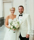 Bride in strapless oscar de la renta wedding dress white bouquet updo hair up groom in white tuxedo