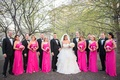 bride in layered alyne ball gown, bridesmaids in one shoulder hot pink gowns from David's Bridal