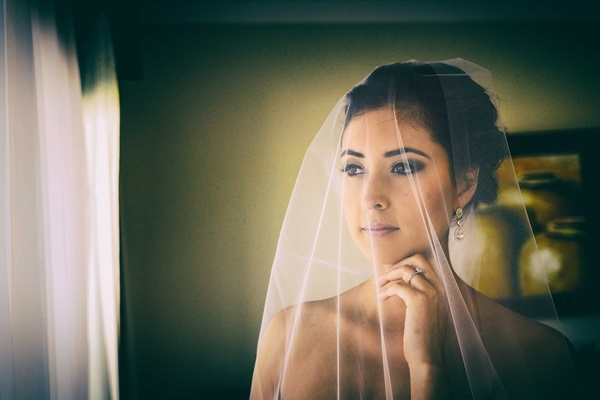 a bride looks out the window with her sheer white veil drawn over her face