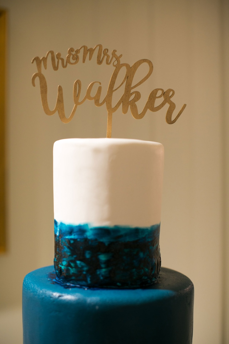 blue and white ocean cake with gold laser-cut mr. and mrs. cake topper