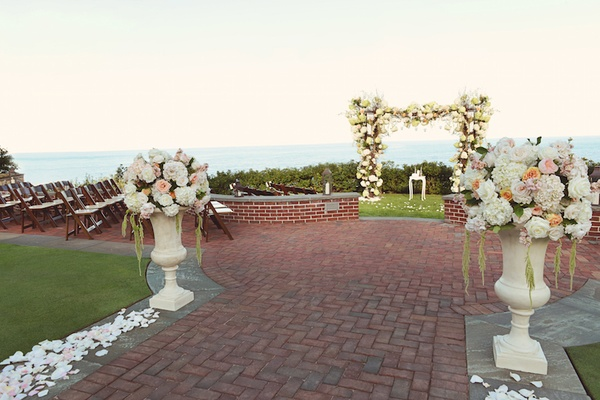 Red brick path with white flower petals and flower chuppah