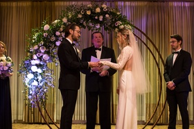 bride and groom exchange rings, circular wedding arch half covered with flowers and greenery