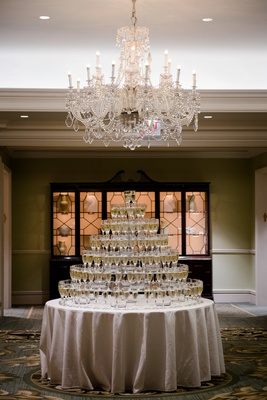 wedding reception ballroom crystal chandelier round table linen champagne tower champagne flutes