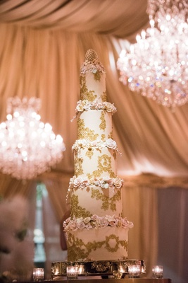Five layer tall wedding cake with gold filigree details and sugar flowers on each tier egg topper