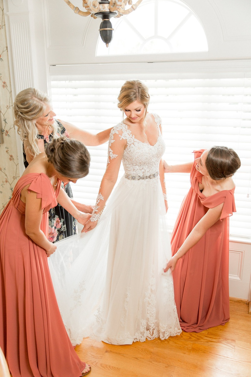 af63d5956 Bride in wedding dress lace long illusion sleeves bridesmaids helping skirt  mother of bride