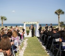oceanfront wedding on lawn, bridal party applauds first kiss between bride and groom