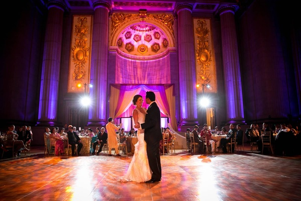 bride and groom share their first dance in the andrew w. mellon auditorium at a purple/gold wedding