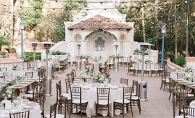 wedding reception courtyard venue wood chairs white linens greenery low centerpieces
