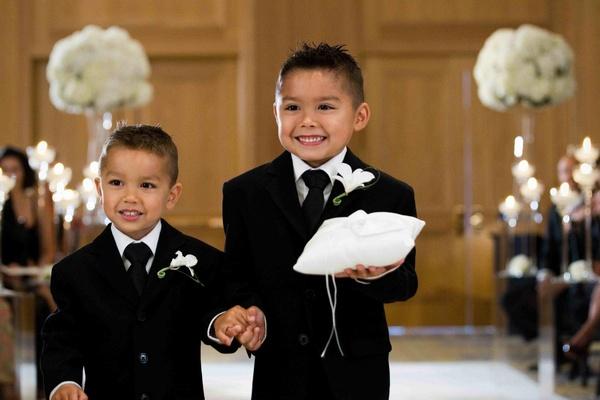 Little boys in tuxedos holding white ring pillow