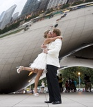 Bride in short dress kisses groom in tuxedo of white coat and black pants in Millennium Park