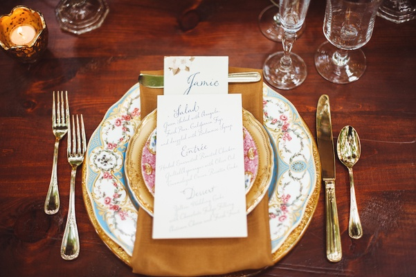 Wedding reception place setting with floral china, golden charger, flatware, napkin