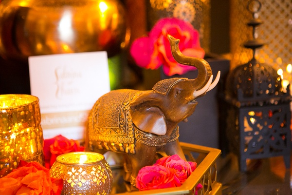 Moroccan-themed engagement party with tray, wood elephant, pink, orange roses, gold votive candles