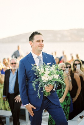wedding ceremony greek wedding mykonos groom in blue suit holding bridal bouquet greenery flowers