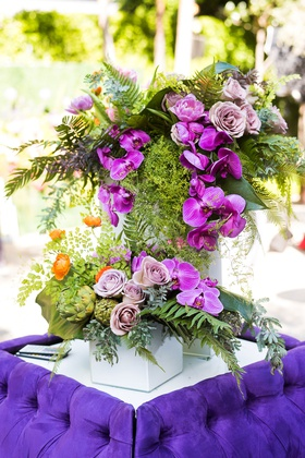 Wedding cocktail hour bright purple tufted settee furniture orchid rose greenery artichoke flowers