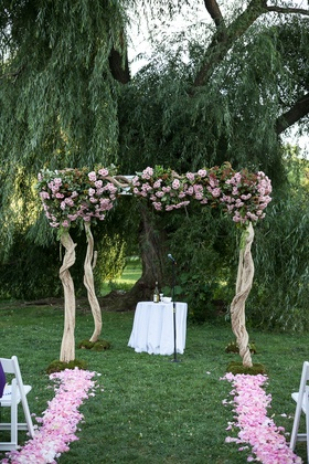 Wood chuppah with pink flowers under outdoor willow tree