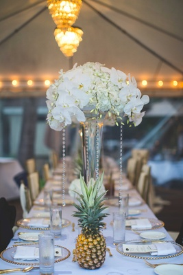 Tall white centerpiece with crystals orchid hydrangea freesia blooms gold beaded charger plates long