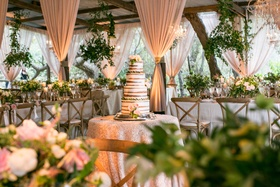 Naked cake with fresh flowers in center of barn venue blush drapery chandeliers foliage