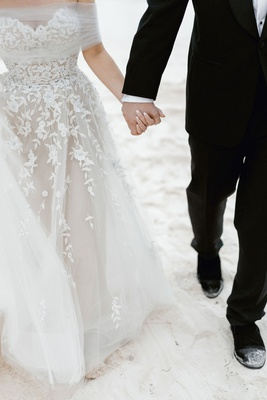 wedding couple bride and groom walking on beach tuxedo formal gown tulle wrap floral appliques