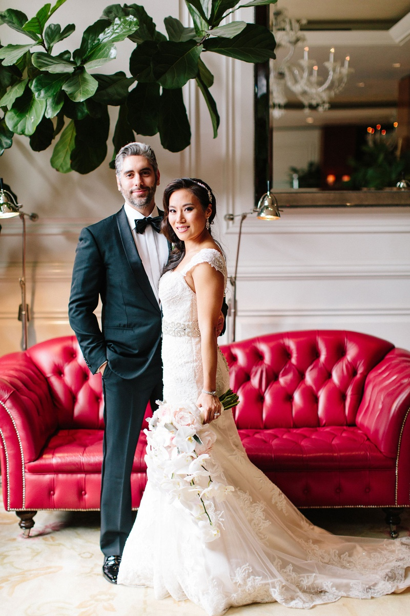 Bride in maggie sottero wedding dress cascading bouquet with groom in tuxedo bow tie red chaise