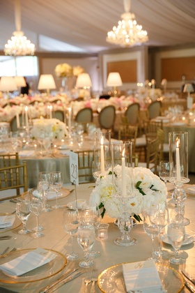 Wedding reception table with golden tablecloth and centerpiece of white peonies, taper candles