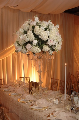 Tall centerpiece of white hydrangea bunches on crystal candle holder