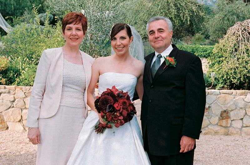 parents stand with bride holding red flower bouquet