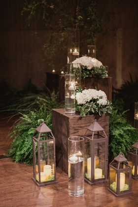 ceremony decor with candles in lanterns, ferns, and white flowers