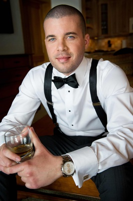 Man in suspenders and bow tie drinking whiskey