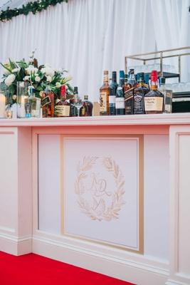 wedding reception bar white with gold monogram red carpet greenery white flowers