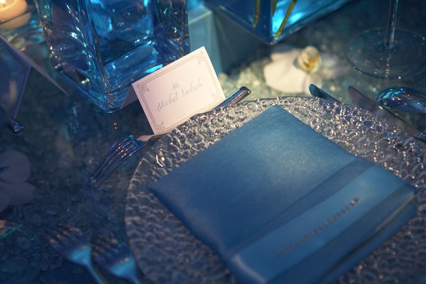 place setting with silver charger and blue napkin