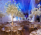 Wedding reception tables with tall gold trumpet vases and white flowers