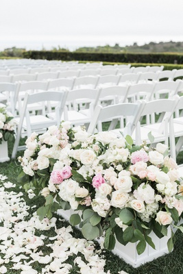 wedding ceremony on grass lawn white flower petals chairs white boxes with greenery pink white