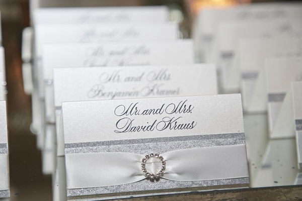 Silver seating card with white ribbon and brooch