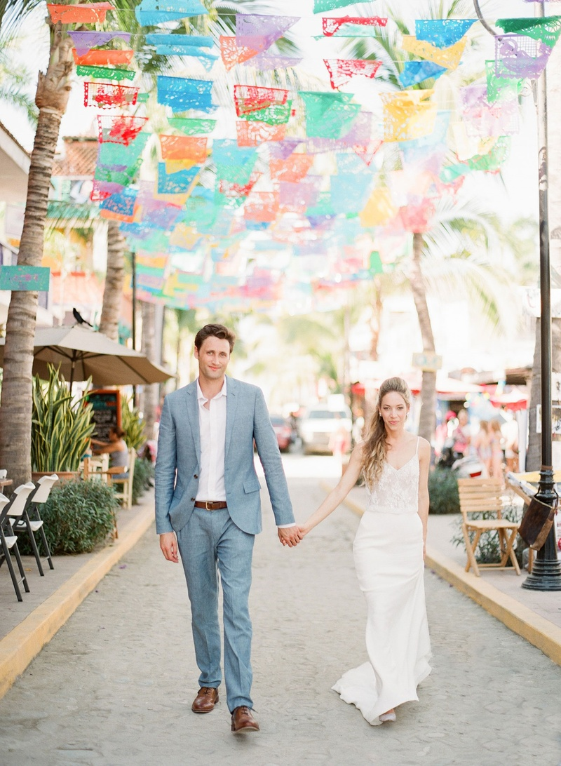 Bride in spaghetti strap v neck wedding dress groom in grey suit light blue under fiesta flags mexic