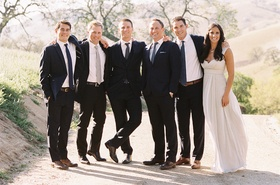 Bride and groom with groomsmen in navy suits and brown shoes
