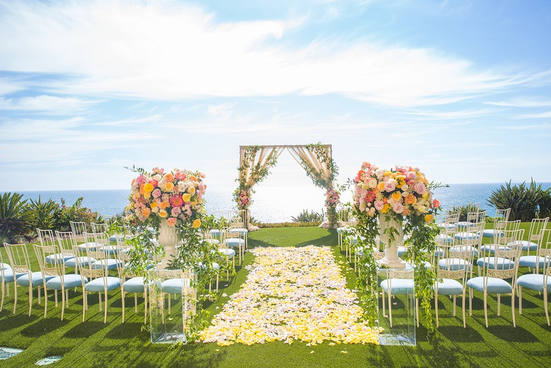 outdoor wedding ceremony yellow flower petal aisle light blue guest seating chameleon chair