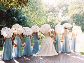 Bride and bridesmaids with backs turned away from camera white lace parasol for bridesmaids guests