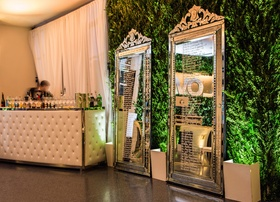 Tufted wet bar and silver standing mirrors