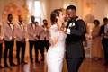 bride in pronovias mermaid wedding dress with lace bodice, groom in tuxedo, first dance