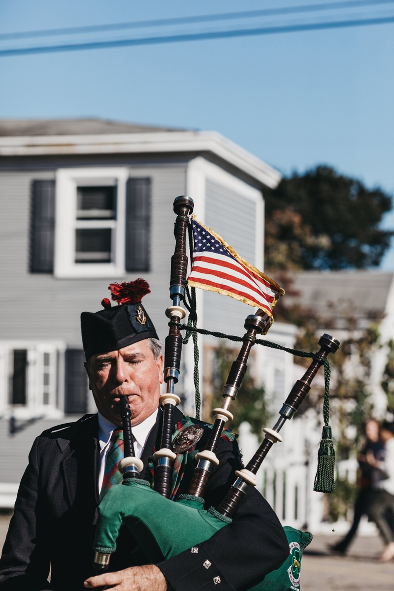 bagpiper with american flag performing outside of church ceremony