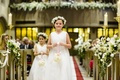 Flower girls in white dresses with head wreaths and pomanders